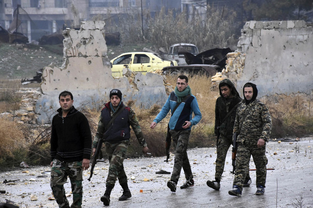 This photo released by the Syrian official news agency SANA, shows Syrian troops and pro-government gunmen marching through the streets of east Aleppo, Syria, Tuesday, Dec. 13, 2016. Syrian rebels ...