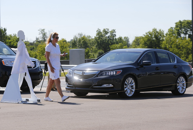 In this July 20, 2015, file photo, a pedestrian crosses in front of a vehicle as part of a demonstration at Mcity on its opening day on the University of Michigan campus in Ann Arbor, Mich. Cars t ...