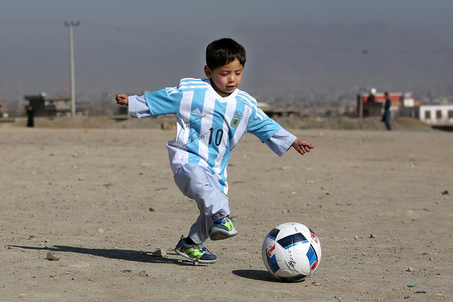 A Friday, Feb. 26, 2016 photo from files of Murtaza Ahmadi, a five-year-old Afghan Lionel Messi fan playing with a soccer ball during a photo opportunity as he wears a shirt signed by Messi, in Ka ...