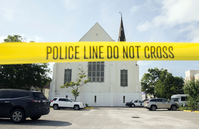 In this June 19, 2015 file photo, police tape surrounds the parking lot behind the AME Emanuel Church as FBI forensic experts work the crime scene, in Charleston, S.C. Prosecutors who wanted to sh ...