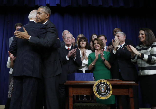 President Barack Obama embraces Vice President Joe Biden after signing the 21st Century Cures Act, Tuesday, Dec. 13, 2016, in the South Court Auditorium in the Eisenhower Executive Office Building ...