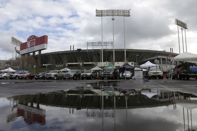 In this Dec. 24, 2015, O.co Coliseum is reflected in a puddle before an NFL football game between the Oakland Raiders and the San Diego Chargers in Oakland, Calif. (Jeff Chiu, File/AP)