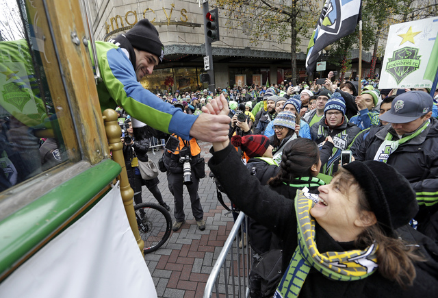 Seattle Sounders midfielder Nicolas Lodeiro reaches to greet a fan before a march and rally celebrating the team's MLS Cup Championship Tuesday, Dec. 13, 2016, in Seattle. Seattle beat Toronto FC  ...