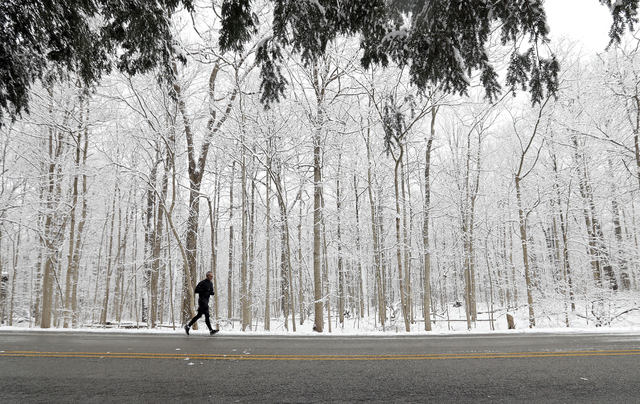 A runner goes for a run in Eagle Creek Park as snow falls Tuesday, Dec. 13, 2016, in Indianapolis. (Darron Cummings/AP)