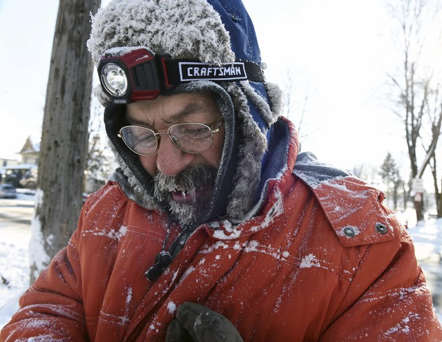 In this Monday, Dec. 12, 2016 photo, ice forms in Carl Bentson's beard and mustache as he clears sidewalks near Colborne Street and St. Clair Avenue in St. Paul, Minn. Temperatures dipped below ze ...