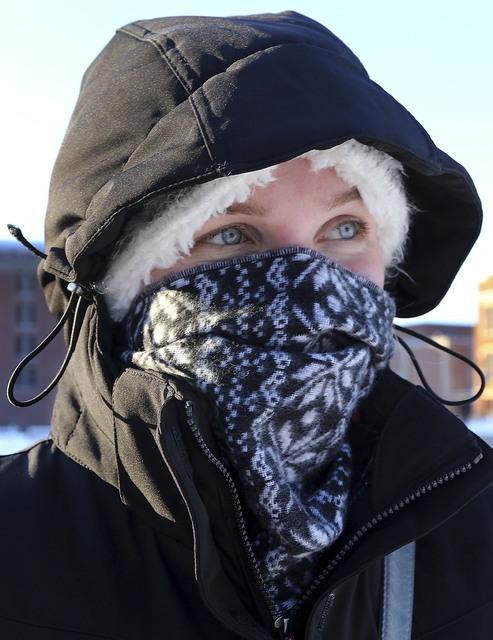 Bundled up for the cold, UW-Eau Claire freshman Rachel Blessinger, of Oak Creek, Wis., walks on campus in Eau Claire on Tuesday, Dec. 13, 2016. (Dan Reiland/The Eau Claire Leader-Telegram via AP)