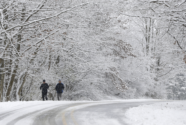 Ken Perry and Stan Ly go for a run in Eagle Creek Park as snow falls Tuesday, Dec. 13, 2016, in Indianapolis. (Darron Cummings/AP)