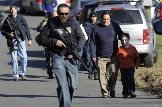 Parents leave a staging area after being reunited with their children following a shooting at the Sandy Hook Elementary School in Newtown, Connecticut, where Adam Lanza fatally shot 27 people, inc ...