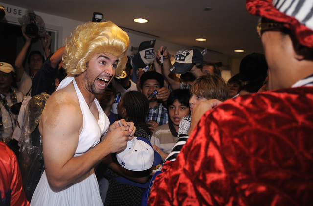 In this Sept. 25, 2008, file photo, Los Angeles Dodgers' Blake DeWitt, left, laughs at Hiroki Kuroda as they sign autographs while wearing costumes as part of rookie hazing, after their Major Leag ...