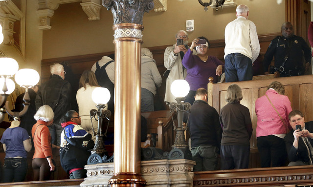 People turn their backs on Electoral College members Monday, Dec. 19, 2016, at the state Capitol as they vote in Topeka, Kan. Kansas' six Republican members of the Electoral College have cast thei ...