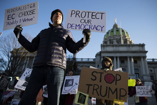 Protesters demonstrate ahead of Pennsylvania's 58th Electoral College at the state Capitol in Harrisburg, Pa., Monday, Dec. 19, 2016. The demonstrators were waving signs and chanting in freezing t ...