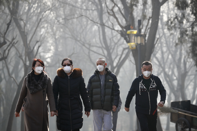 Chinese people wearing masks for protection against pollution exercise at Ritan Park during a heavily polluted day in Beijing, Monday, Dec. 19, 2016. Chinese cities are limiting the number of cars ...