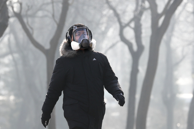 A man wearing a mask for protection against pollution exercise at Ritan Park during a heavily polluted day in Beijing, Monday, Dec. 19, 2016. Chinese cities are limiting the number of cars on road ...
