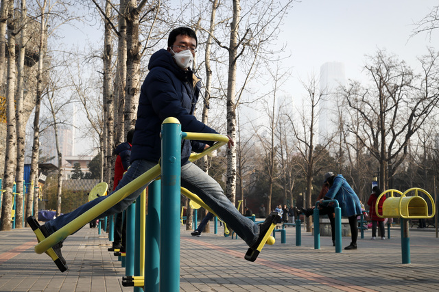 A Chinese wearing a mask for protection against pollution exercises at Ritan Park as capital city is shrouded by heavy smog in Beijing, Monday, Dec. 19, 2016. Chinese cities are limiting the numbe ...
