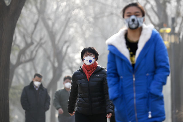 Chinese people wearing masks for protection against pollution walk at Ritan Park shrouded by heavy smog in Beijing, Monday, Dec. 19, 2016. Chinese cities are limiting the number of cars on roads a ...