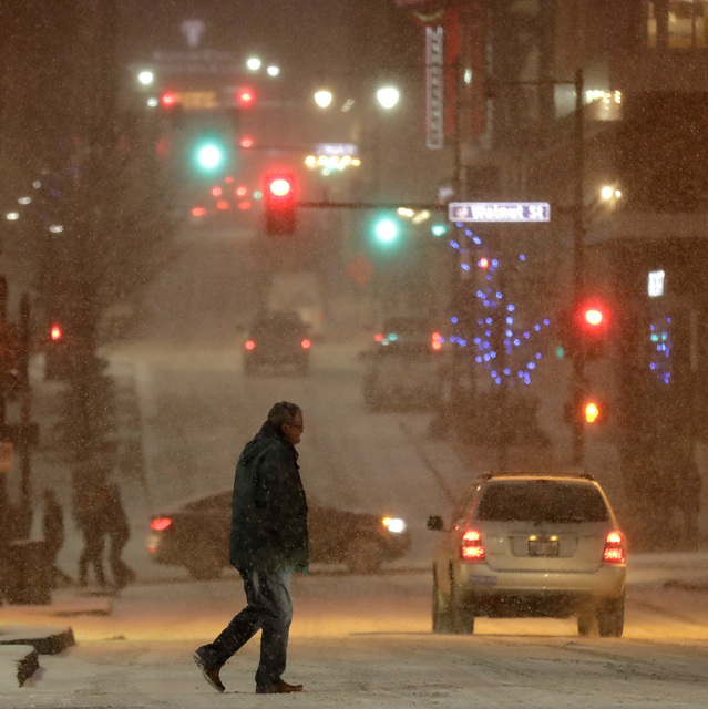 A pedestrian walks across a street in downtown Kansas City, Mo., on Saturday, Dec. 17, 2016. A winter storm of snow, freezing rain and bone-chilling temperatures hit the nation's mid-section and E ...