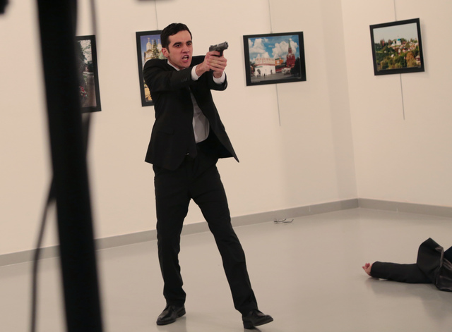 An unnamed gunman gestures after shooting the Russian Ambassador to Turkey, Andrei Karlov, at a photo gallery in Ankara, Turkey, Monday, Dec. 19, 2016. The Russian foreign ministry spokeswoman sai ...