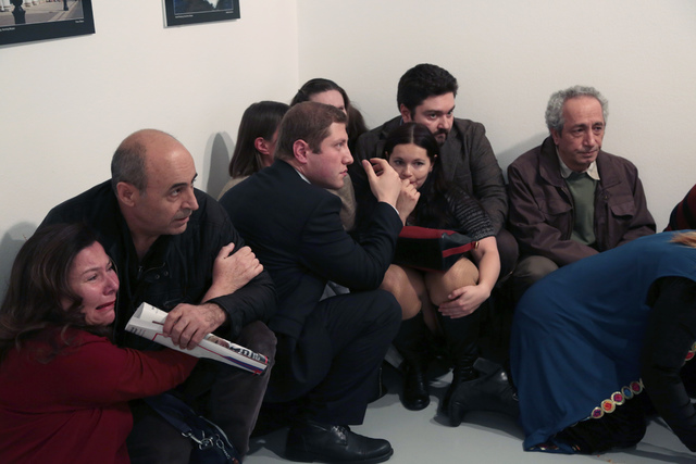 People crouch in a corner after Andrei Karlov, the Russian Ambassador to Turkey, was shot at a photo gallery in Ankara, Turkey, Monday, Dec. 19, 2016. Karlov, 62, was several minutes into a speech ...