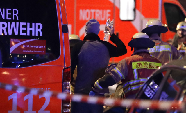 Firefighters attend an injured person after a truck ran into crowded Christmas market in Berlin, Germany, Monday, Dec. 19, 2016. Police said that several people have been killed. (AP Photo/Michael ...