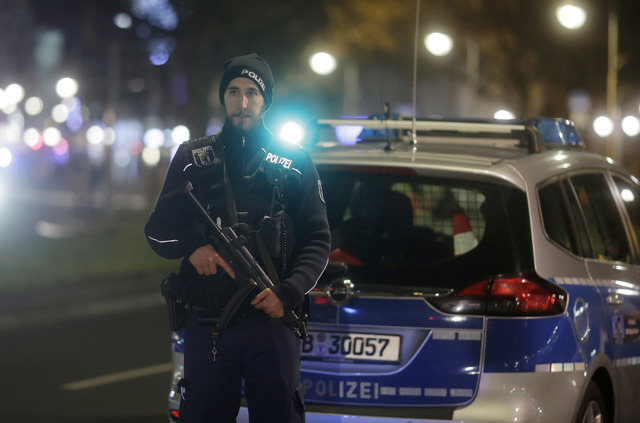 A police officer with a submachine gun stands guard after a truck ran into a crowded Christmas market in Berlin, Germany, Monday, Dec. 19, 2016. Several people have been killed in the incident. (A ...