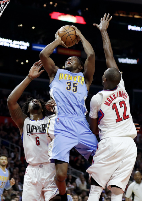 Denver Nuggets forward Kenneth Faried, middle, shoots between Los Angeles Clippers center DeAndre Jordan, left, and forward Luc Mbah a Moute during the second half of an NBA basketball game in Los ...