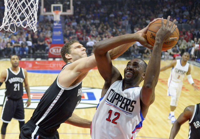 This is a Monday, Feb. 29, 2016 file photo Los Angeles Clippers forward Luc Mbah a Moute, right, of Cameroon, shoots as Brooklyn Nets center Brook Lopez defends during the first half of an NBA bas ...