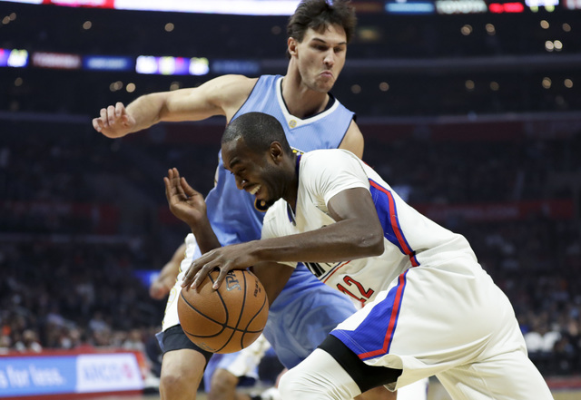 Los Angeles Clippers forward Luc Mbah a Moute, drives to the basket past Denver Nuggets forward Danilo Gallinari during the first half of an NBA basketball game in Los Angeles, Tuesday, Dec. 20, 2 ...
