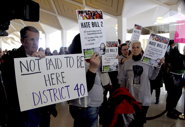 Opponents of HB2 hold signs outside the North Carolina House chambers gallery as the North Carolina General Assembly convenes for a special session at the Legislative Building in Raleigh, N.C. on  ...