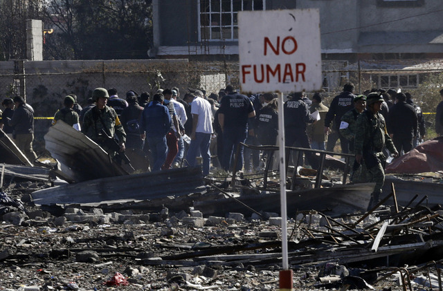 A no smoking sign stands above the scorched rubble of the open-air San Pablito fireworks market that exploded in Tultepec on the outskirts of Mexico City, Wednesday, Dec. 21, 2016. The market was  ...