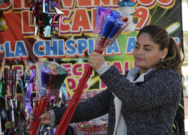 A woman looks at fireworks for sale a the Jaltenco Market in Zumpango, Mexico, Wednesday, Dec. 21, 2016.  On Tuesday, a larger fireworks market in Tultepec exploded, killing and injuring dozens. ( ...