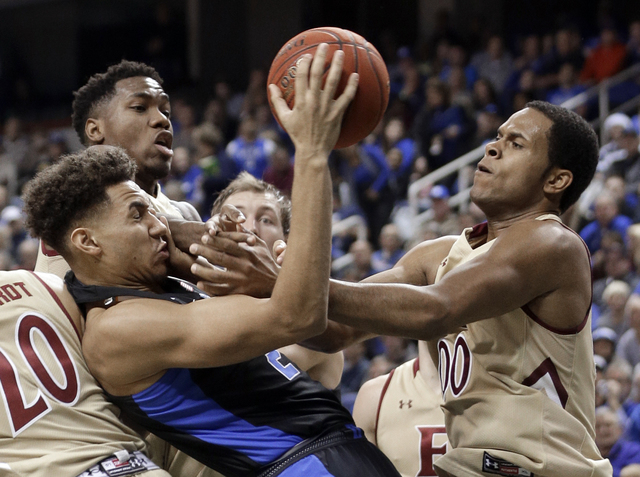 Duke's Chase Jeter, left, and Elon's Steven Santa Ana, right, battle for a rebound in the first half of an NCAA college basketball game in Greensboro, N.C., Wednesday, Dec. 21, 2016. (AP Photo/Chu ...