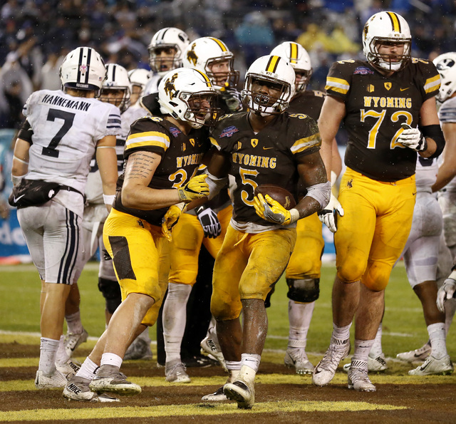 Wyoming running back Brian Hill (5) celebrates with teammates after scoring a touchdown during the first half of the Poinsettia Bowl NCAA college football game against BYU on Wednesday, Dec. 21, 2 ...