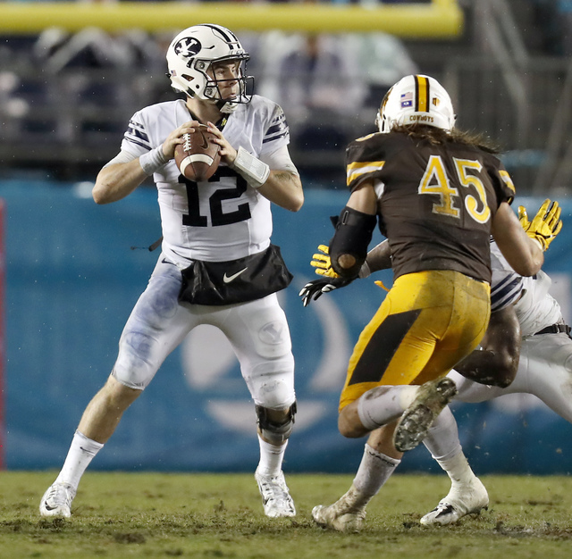 BYU quarterback Tanner Mangum, left, looks to pass against Wyoming during the first half of the Poinsettia Bowl NCAA college football game Wednesday, Dec. 21, 2016, in San Diego. (AP Photo/Ryan Kang)