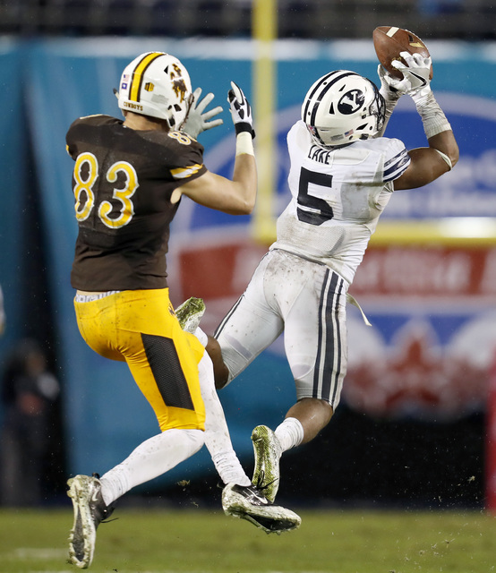 BYU defensive back Dayan Lake, right, intercepts the football in front of Wyoming wide receiver Jake Maulhardt, left, on a pass by quarterback Josh Allen during the first half of the Poinsettia Bo ...