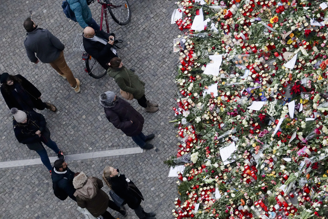 People stand near candles at the Christmas market, three days after a truck ran into the crowd and killed several people, near the Kaiser Wilhelm Memorial Church in Berlin, Thursday, Dec. 22, 2016 ...