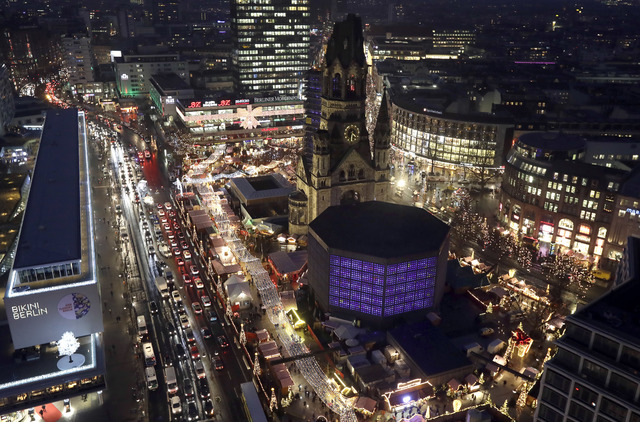 Cars drive past the reopened Christmas market at the Kaiser Wilhelm Memorial Church, center, in Berlin, Germany, Thursday, Dec. 22, 2016, three days after a truck ran into the crowded market and k ...