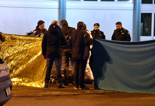 Italian police cordon off an area around a body after a shootout between police and a man in Milan's Sesto San Giovanni neighborhood, early Friday, Dec. 23, 2016. Italy's interior minister Marco M ...