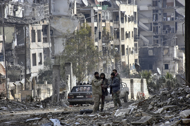 This photo released by the Syrian official news agency SANA, shows Syrian troops and pro-government gunmen stand in the Ansari neighborhood, east Aleppo, Syria, Friday, Dec 23, 2016. On Thursday,  ...