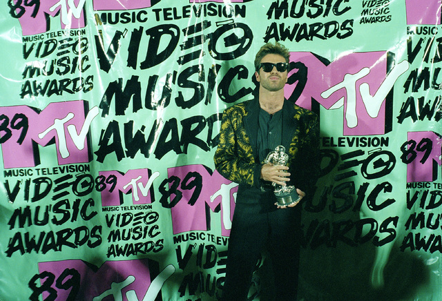 """In this Wednesday, Sept. 6, 1989, photo, musician George Michael holds his trophy after winning the 1989 Video """"Vanguard Award"""" for his """"Father Figure"""" video during the MTV Music Awards at the Uni ..."""