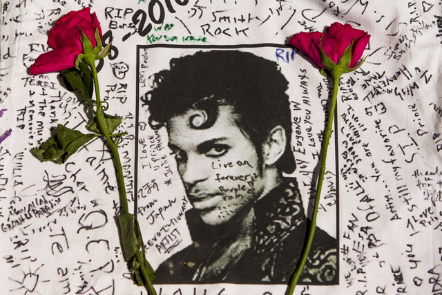 In this April 22, 2016, photo, flowers lie on a T-shirt signed by fans at a makeshift memorial for musician Prince outside the Apollo Theater in New York. The singer died April 21, 2016, at the ag ...