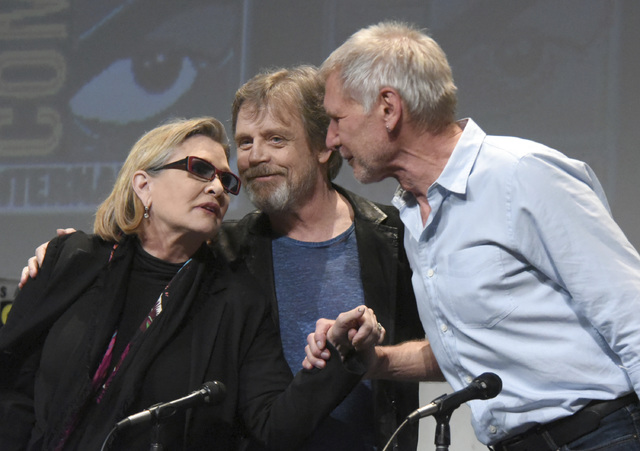 In this Friday, July 10, 2015, photo, from left, Carrie Fisher, Mark Hamill and Harrison Ford attend a panel at Comic-Con International in San Diego, Calif. On Tuesday, Dec. 27, 2016, a family pub ...