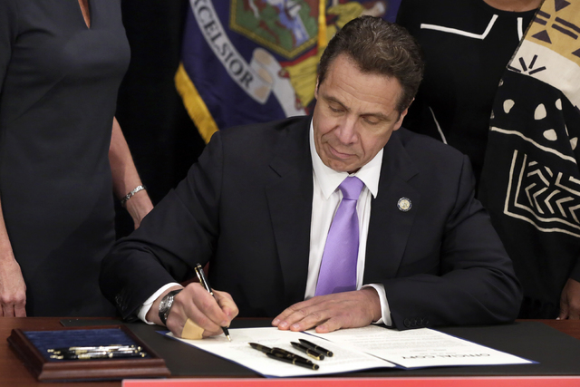 In this April 4, 2016, photo, New York Gov. Andrew Cuomo signs a law that will gradually raise New York's minimum wage to $15, at the Javits Convention Center, in New York. (Richard Drew/Pool, Fil ...