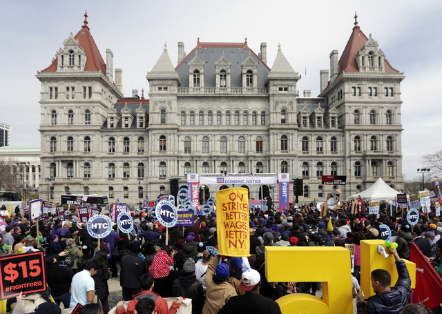 The state Capitol provides a backdrop March 15, 2016, as supporters of a $15 minimum wage rally at the Empire State Plaza in Albany, N.Y. (Mike Groll/File, AP)