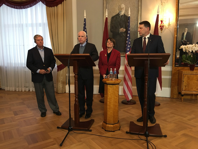 Latvian President Raimonds Vejonis, right, looks at  US Sen. John McCain centre left, during a press conference,  Wednesday, Dec. 28, 2016 in Riga, Latvia, while Lindsey Graham, R-SC., and Amy Klo ...