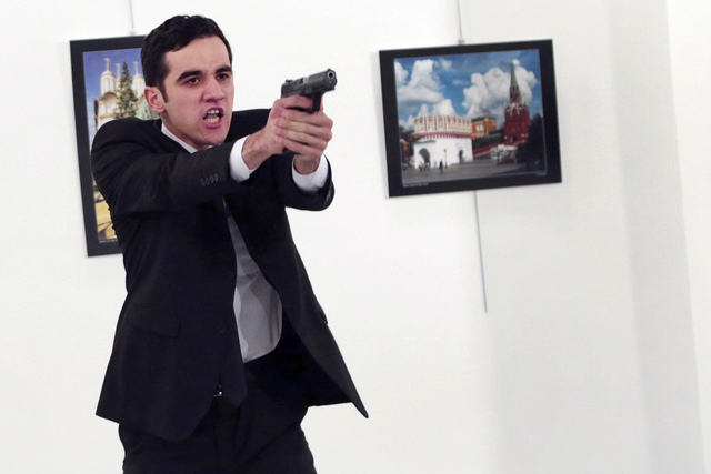 A man identified as Mevlut Mert Altintas holds up a gun after shooting Andrei Karlov, the Russian Ambassador to Turkey, at a photo gallery in Ankara, Turkey, Monday, Dec. 19, 2016. Police killed t ...