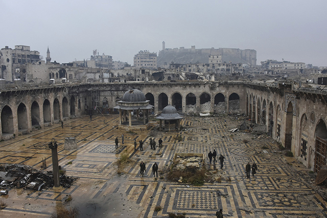 Syrian troops and pro-government gunmen walk inside the destroyed Grand Umayyad mosque in the old city of Aleppo, Syria, Tuesday, Dec. 13, 2016. (SANA via AP)