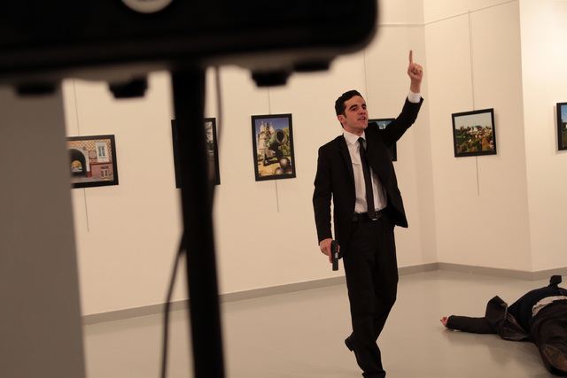 A man gestures near to Andrei Karlov on ground,  the Russian Ambassador to Turkey at a photo gallery in Ankara, Turkey, Monday, Dec. 19, 2016. An Associated Press photographer says a gunman has fi ...