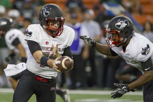 UNLV quarterback Dalton Sneed, left, hands off the football to running back Lexington Thomas, right, during the first quarter of an NCAA college football game against Hawaii, Saturday, Oct. 15, 20 ...