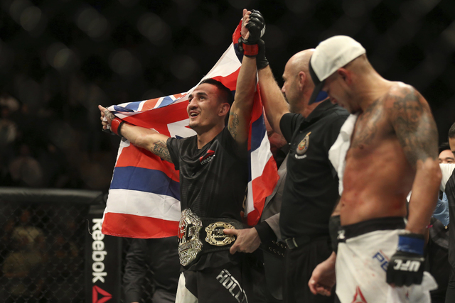 Max Holloway celebrates after defeating Anthony Pettis, right, to win the interim featherweight title during the main event of a mixed martial arts bout at UFC 206, Saturday, Dec. 10, 2016, at the ...