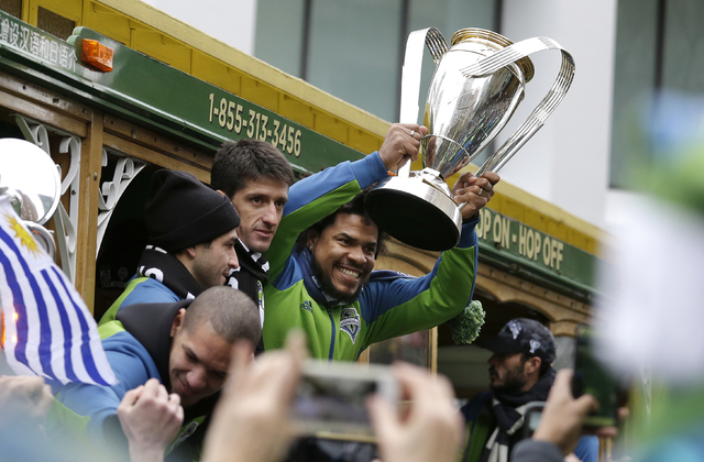 Seattle Sounders' Roman Torres holds the MLS Cup Championship trophy as the team begins a march and rally celebrating their victory, Tuesday, Dec. 13, 2016, in Seattle. Seattle beat Toronto FC 5-4 ...